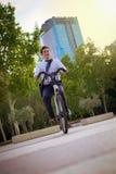 工作的年轻buinessman骑马在城市 图库摄影