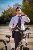 工作的年轻businessmanriding在城市 免版税库存照片