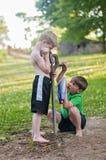 工作的男孩从一口干燥井填装二花紫树 库存图片