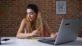 工作的白肤金发的白种人女性中断输入膝上型计算机和检查她的智能手机充满巨大惊奇和 股票视频