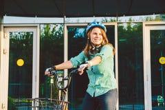 工作的题材在自行车 一名年轻白种人妇女在不伤环境的运输自行车到达了到办公室 女孩在bic中 库存图片