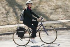 工作的骑自行车的女实业家 免版税库存图片