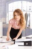 工作的年轻可爱的时装设计师 免版税库存照片