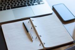 工作空间,顶视图 膝上型计算机、手机和开放笔记本有笔的在米黄桌面上 免版税库存照片