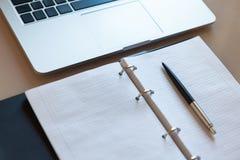 工作空间,顶视图 膝上型计算机和开放笔记本有笔的在米黄桌面上 免版税库存照片