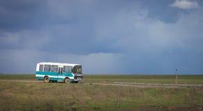 工作站立在下覆盖的领域的公共汽车在 风景 免版税库存照片