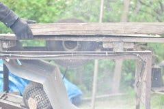 工作者与圆锯的切口木头 库存照片