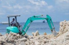 工作者与挖掘机的聚集沙子在建造场所 免版税库存照片