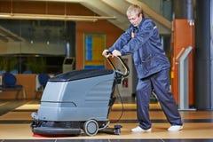 工作者与机器的清洁地板 免版税库存图片