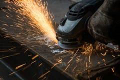 工作者与研磨机的剪切金属 发火花,当研铁时 免版税库存照片
