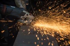 工作者与研磨机的剪切金属 发火花,当研铁时 免版税图库摄影