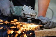 工作者与研磨机的剪切金属 免版税图库摄影