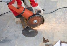 工作者与研磨机的剪切金属 免版税库存图片