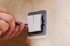 工作者人电工修理在公寓的损坏的开关,新的特写镜头的设施 免版税库存图片