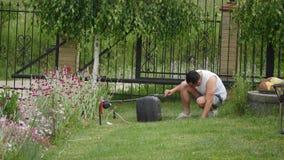 工作者人震动倾吐从割草机袋子的草入独轮车 庭院草甸草坪切口 夏天在庭院里运作 股票视频