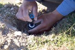 工作者修理草坪喷水隆头 库存照片