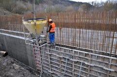 工作者倾吐混凝土入墙壁的模板 免版税库存图片