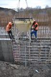工作者倾吐混凝土入墙壁的模板 库存图片