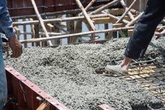 工作者倾吐的混凝土在建造场所运作 免版税库存图片