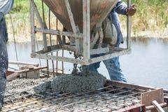 工作者倾吐的混凝土在建造场所运作 免版税图库摄影