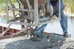 工作者倾吐的混凝土在建造场所运作 免版税库存照片
