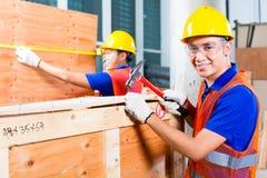 工作者关闭有锤子和钉子的木箱子 免版税库存图片