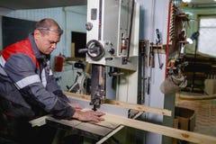 工作者切开在一个曲线锯的机器的一个酒吧 免版税库存照片
