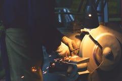 工作者削尖在一个转动的砂轮的工具 图库摄影