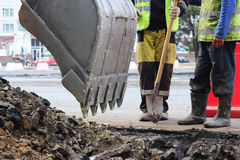 工作者加深与一种挖掘机的路坑进一步修理和涂柏油的 免版税库存图片