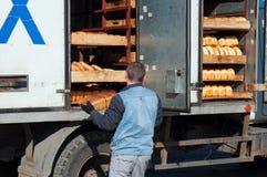 工作者卸载从卡车的新鲜面包 图库摄影