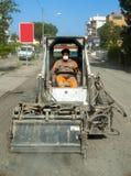 工作者司机滑行操舵取消破旧的沥青 免版税库存照片