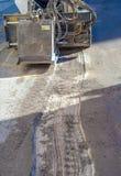 工作者司机滑行操舵取消破旧的沥青 库存图片