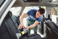 工作者吸尘的和清洗的汽车 汽车保养和详述的概念 库存照片