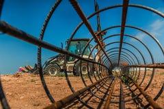 工作者和一台拖拉机有一个钻设备的在建筑s 免版税图库摄影