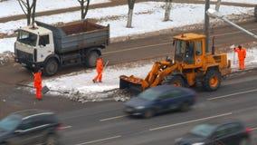 工作者和清除在街道上的雪的拖拉机 股票视频