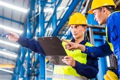 工作者和铲车司机在工业工厂 免版税图库摄影
