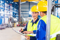 工作者和铲车司机在工业工厂 库存图片