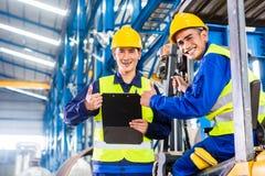 工作者和铲车司机在工业工厂 库存照片