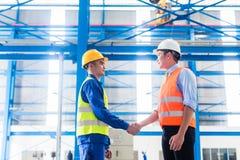 工作者和顾客有协议在工厂 库存照片