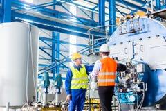 工作者和经理在工业工厂 图库摄影
