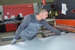 工作者哺养的金属板到机器里 库存图片