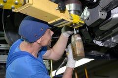 工作者固定在细节汽车底部 汇编传动机o 免版税库存图片