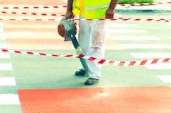 工作者土和尘土清洁路以吹的机器沥青为绘新的自行车道做准备与红色油漆 免版税库存照片