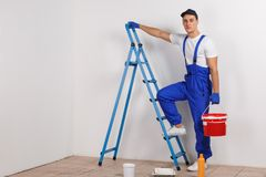 工作者在与一个桶的一架梯子上升在白色背景 库存图片