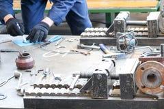 工作者在与一个金属制品工具的一张桌上工作在工厂,工厂 概念产业,在工厂的工作,测量si 免版税库存图片