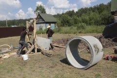 工作者在井安装具体圆环 免版税图库摄影