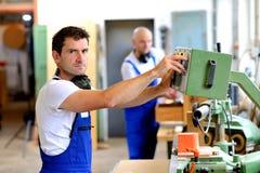 工作者在使用机器的工厂 免版税库存图片