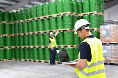 工作者在有油桶的一个仓库检查股票 库存图片