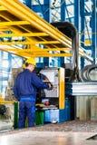 工作者在机器控制盘区的制造工厂 库存照片