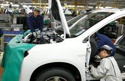 工作者在汽车工厂装配在装配线的一辆汽车 免版税库存照片